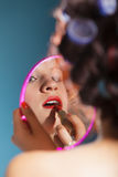 La aplicación de la muchacha compone el lápiz labial rojo Fotos de archivo