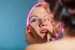 La aplicación de la muchacha compone el lápiz labial rojo Imagenes de archivo