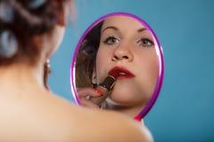 La aplicación de la muchacha compone el lápiz labial rojo Fotografía de archivo