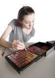 La aplicación de la mujer joven compone de la paleta grande Fotos de archivo libres de regalías