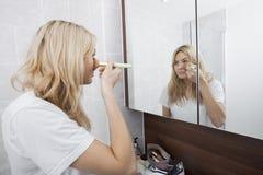 La aplicación de la mujer joven se ruboriza mientras que mira el espejo en cuarto de baño Foto de archivo