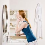 La aplicación de la mujer se ruboriza con el cepillo del maquillaje Foto de archivo