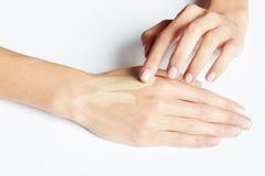 La aplicación de la mano de una mujer compone en la piel foto de archivo