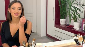 La aplicación de la mujer componen y la mirada a través del espejo en el tiempo de mañana almacen de metraje de vídeo