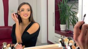 La aplicación de la mujer componen y la mirada a través del espejo en el tiempo de mañana almacen de video