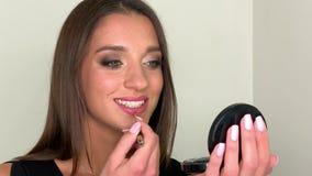 La aplicación de la mujer componen y la mirada a través del espejo en el tiempo de mañana metrajes