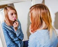 La aplicación del adolescente compone en su cara, poniendo en lipstic rosado Fotografía de archivo libre de regalías