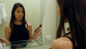 La aplicación del adolescente de la belleza componen y la admiración en el espejo Imagen de archivo