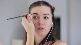 La aplicación del adolescente de la belleza componen y la admiración en el espejo Mujeres atractivas que miran en el espejo en ca metrajes