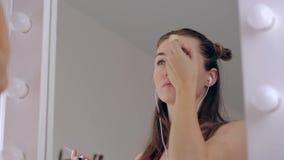 La aplicación del adolescente de la belleza componen y la admiración en el espejo Mujeres atractivas que miran en el espejo en ca almacen de metraje de vídeo
