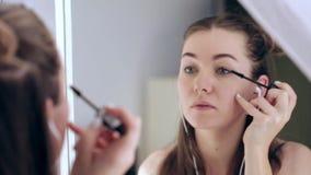 La aplicación del adolescente de la belleza componen y la admiración en el espejo Mujeres atractivas que miran en el espejo en ca almacen de video