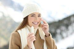 La aplicación feliz de la mujer hidrata la crema en cara imagen de archivo libre de regalías