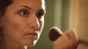 La aplicación femenina joven atractiva se ruboriza con el cepillo delante del espejo almacen de metraje de vídeo