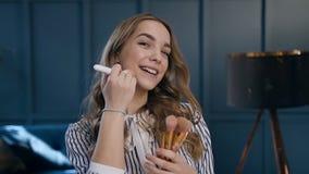 La aplicación linda feliz de la mujer se ruboriza en los pómulos usando cepillo rosado en el cuarto almacen de video