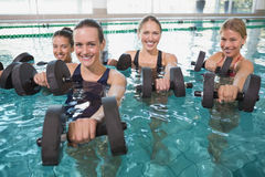 La aptitud femenina sonriente clasifica hacer aeróbicos de la aguamarina con pesas de gimnasia de la espuma Imagen de archivo