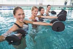 La aptitud femenina sonriente clasifica hacer aeróbicos de la aguamarina con pesas de gimnasia de la espuma Fotografía de archivo libre de regalías