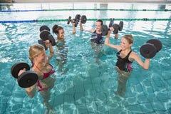 La aptitud femenina sonriente clasifica hacer aeróbicos de la aguamarina con pesas de gimnasia de la espuma Fotografía de archivo