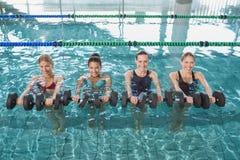 La aptitud femenina sonriente clasifica hacer aeróbicos de la aguamarina con pesas de gimnasia de la espuma Fotos de archivo