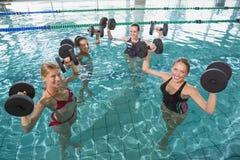 La aptitud femenina sonriente clasifica hacer aeróbicos de la aguamarina con pesas de gimnasia de la espuma Foto de archivo libre de regalías