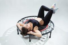 La aptitud-muchacha joven hace ejercicios en rebounder Imagen de archivo