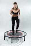 La aptitud-muchacha linda hace ejercicio en rebounder Imagenes de archivo