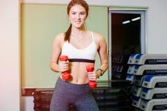 La aptitud, muchacha toma aeróbicos del paso con pesas de gimnasia Foto de archivo