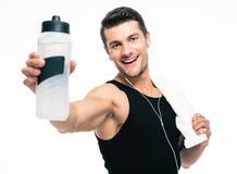 La aptitud sonriente sirve sostener la toalla y la botella con agua Foto de archivo libre de regalías