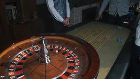 La apuesta salta - a la gente de la ruleta del casino que juega la ruleta en un casino rojo 34 metrajes