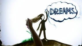 La arena del dibujo, manos del hombre escribe sueños de la palabra al lado de muchacha de la arena en la pantalla almacen de video