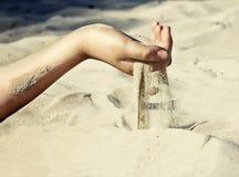 La arena está vertiendo a través de sus fingeres Foto de archivo libre de regalías