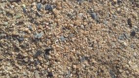 La arena, los cantos rodados y las pequeñas rocas eran gránulos negros mezclados con grava Foto de archivo