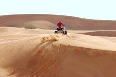La arena vuela hacia fuera de debajo las ruedas del ATV foto de archivo