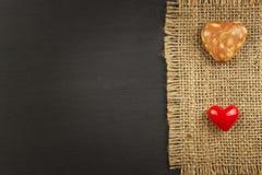 La arpillera vieja en un tablero de madera negro con oye Imagenes de archivo