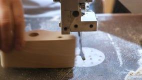 La artesana está cortando un objeto de madera de la madera con la sierra de cinta Manos del primer