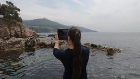 la Asiático-mirada de la muchacha turística toma imágenes de las islas, de las rocas y del mar en Turquía almacen de video