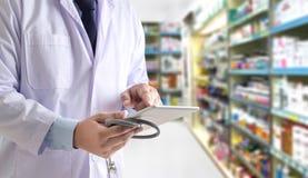 La atención sanitaria de trabajo de la droguería del técnico de la farmacia del farmacéutico imagenes de archivo