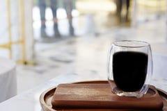 La atmósfera en la tienda con una taza de café con un fondo y una luz borrosos imagen de archivo