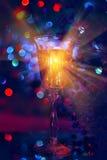 La atmósfera festiva por la tarde con un vidrio del champán y de un arco iris coloreó el bokeh Fotografía de archivo