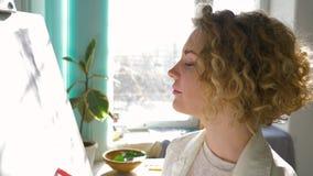 La atmósfera inspiradora, mujer feliz de los artistas goza el planear de la nueva pintura en lona blanca limpia en el caballete e almacen de metraje de vídeo