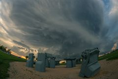 La atracción turística de Nebraska titulada 'Carhenge 'con una tempestad de truenos severa en el fondo imagenes de archivo
