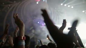 La audiencia aplaude alegre las manos que aplauden en aire en un lumiere de la luz que destella del concierto al ejecutante metrajes