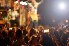 La audiencia con las manos aumentó en un festival y las luces de música que fluían abajo desde arriba de la etapa Fotografía de archivo libre de regalías