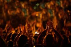La audiencia con las manos aumentó en un festival y las luces de música que fluían abajo desde arriba de la etapa Imágenes de archivo libres de regalías