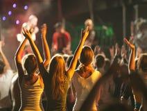 La audiencia con las manos aumentó en un festival y las luces de música que fluían abajo desde arriba de la etapa Fotografía de archivo