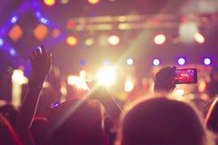 La audiencia con las manos aumentó en un festival y las luces de música que fluían abajo desde arriba de la etapa Foco suave, mov Foto de archivo