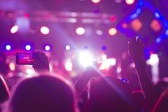 La audiencia con las manos aumentó en un festival y las luces de música que fluían abajo desde arriba de la etapa Foco suave, mov Foto de archivo libre de regalías