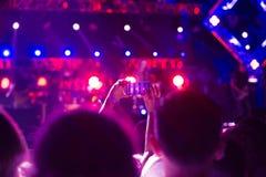 La audiencia con las manos aumentó en un festival y las luces de música que fluían abajo desde arriba de la etapa Foco suave, mov Imagen de archivo