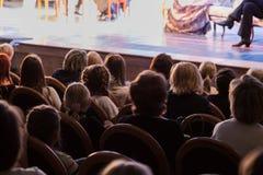 La audiencia en el teatro que mira un juego La audiencia en el pasillo: adultos y niños Imagenes de archivo