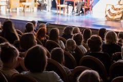 La audiencia en el teatro que mira un juego La audiencia en el pasillo: adultos y niños Imagen de archivo