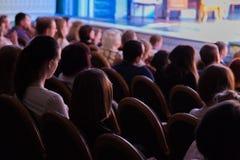 La audiencia en el teatro que mira un juego La audiencia en el pasillo: adultos y niños Imagen de archivo libre de regalías